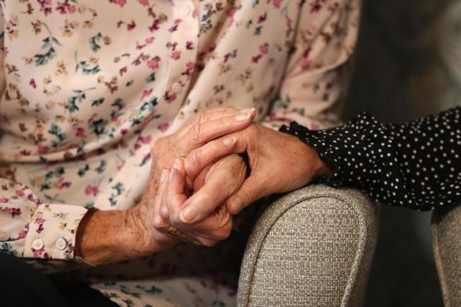 A care home resident holds hands with her daughter (Andrew Matthews/PA)