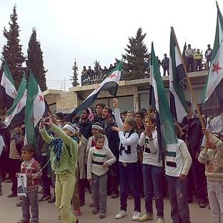 Anti-Syrian regime protesters wave the Syrian revolution flags during a protest in Idlib, northern Syria (AP/Idlib News Network)