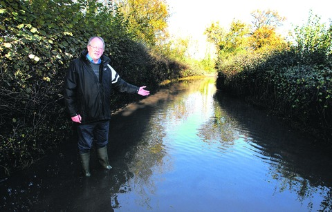 WATER, WATER EVERYWHERE: Wellington-clad Councillor Paul Tuthill on the affected stretch of Lower Howsell Lane near Malvern Link. Picture 45169101