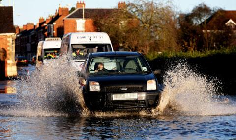 SPLASHING TIME: Cars make their way carefully along Pershore's flooded High Street.