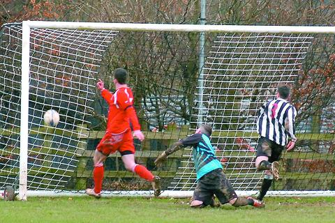 FINAL COUNTDOWN: Tom Boyle seals Ledbury Town's win, drilling in the visitors' third against Bartestree in the HFA Challenge Cup semi-final. Picture: JAMES MAGGS.