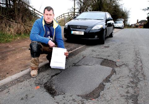 FURIOUS: Derek Jones from Littleworth, with the pothole in Church Lane that caused £165 damage to his car. 0913258902