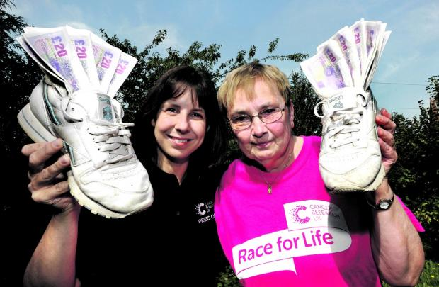RALLYING CALL: Janet Burley, right, hands over more than £1,000 to Cancer Research press officer Paula Young after taking part in June's Race for Life event around Pitchcroft racecour