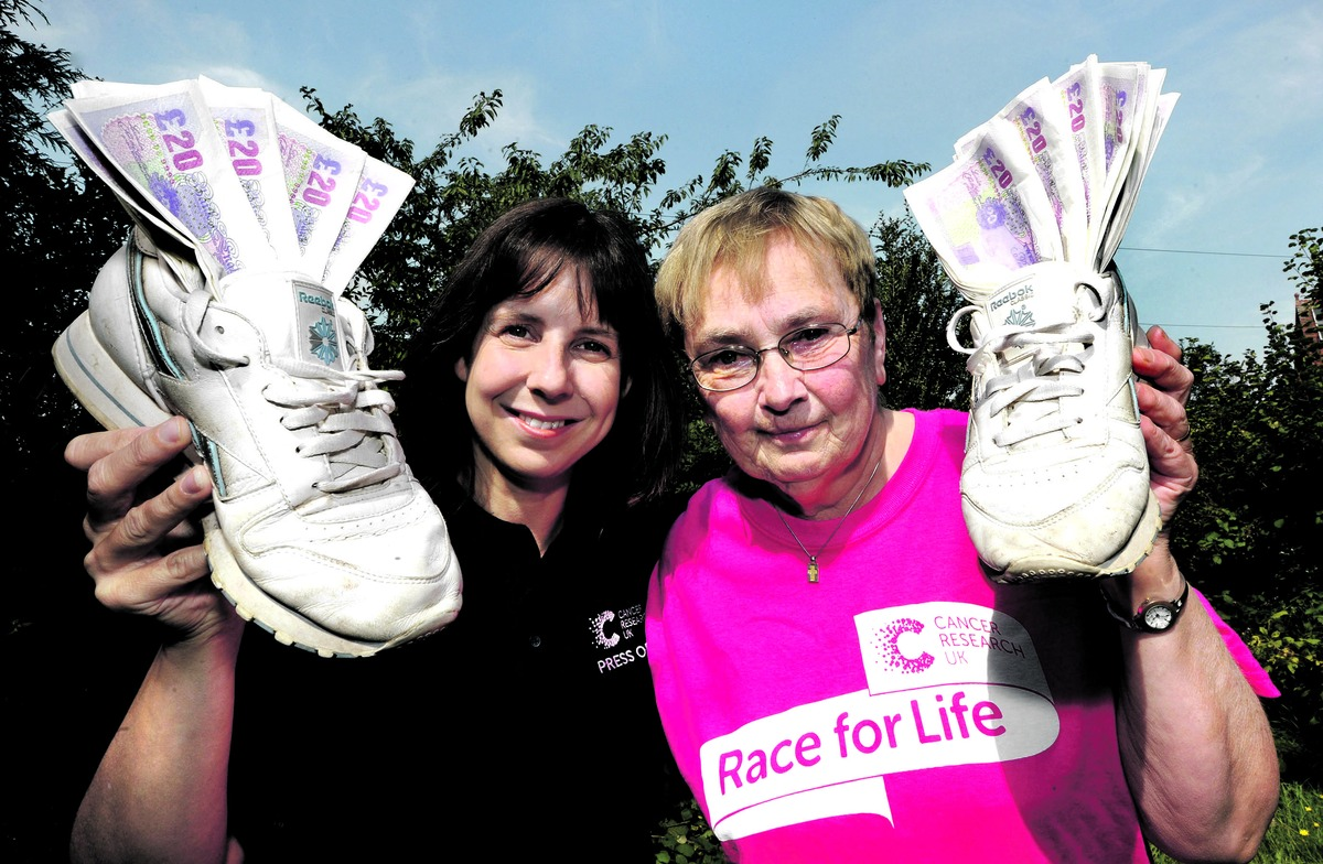 RALLYING CALL: Janet Burley, right, hands over more than £1,000 to Cancer Research press officer Paula Young after taking part in June's Race for Life event around Pitchcroft racecourse in Worcester. Picture by John Anyon 3513391701