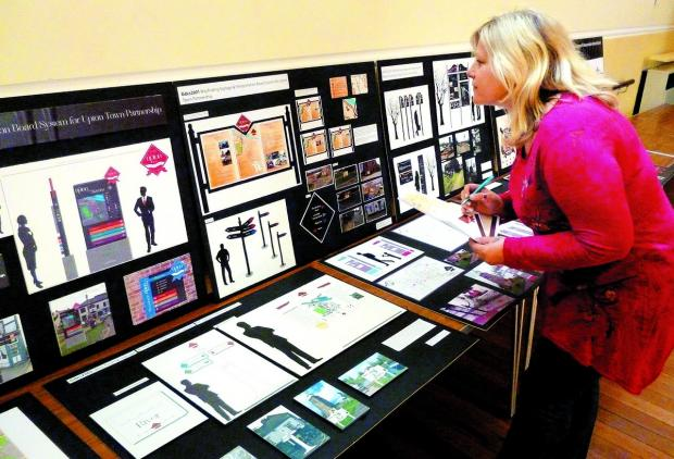 SOME OF THE DESIGNS: A member of the public inspects the students' many designs.