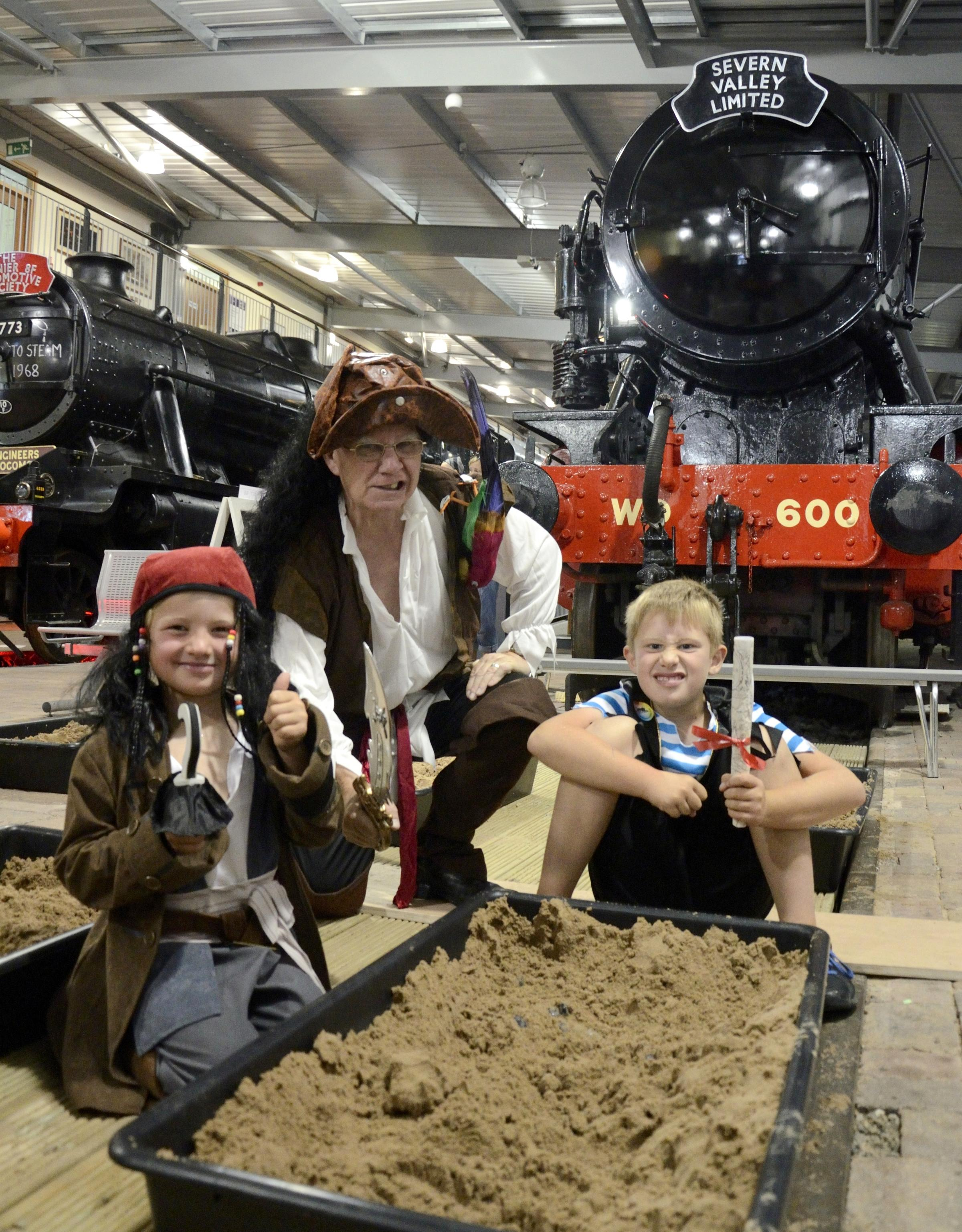 William Murdock, aged seven, Charlie Murdock, four, and 'Captain' Geoff (Engine House volunteer) enjoying activities at The Engine Hous