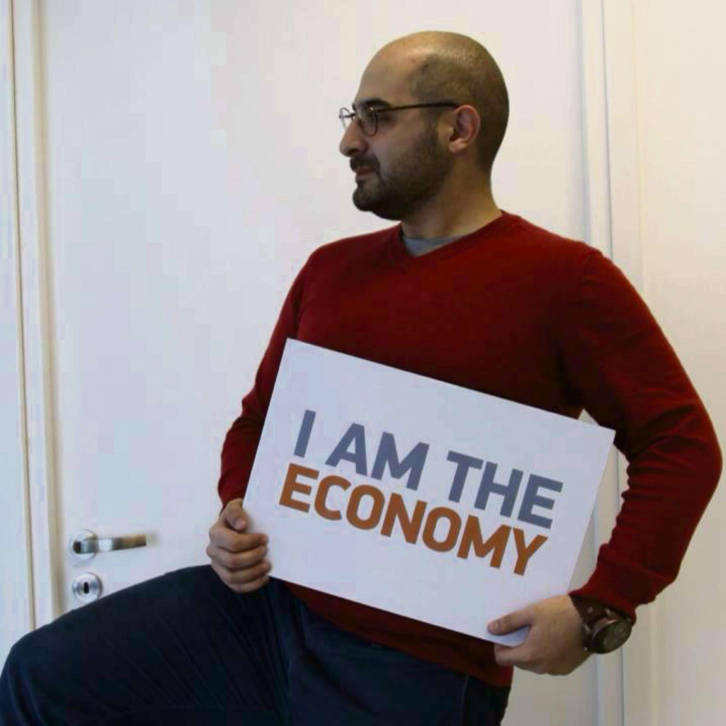 Constantinos Arkadiou holding the I Am The Econ