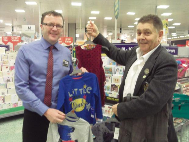 Morrisons manager Steve Guoite hands the clothing over to Martin Lawrence, Octagon trustee.