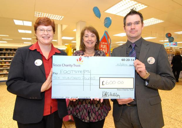 1114542501. 12/03/14. Tesco £600 cheque presentation to Footsteps. Left to right - community champion at the St Peter's Tesco store Joanne Jenkins, Sue Smith from Footsteps and acting store manager Stuart Gillett with the cheque. Picture by Nick