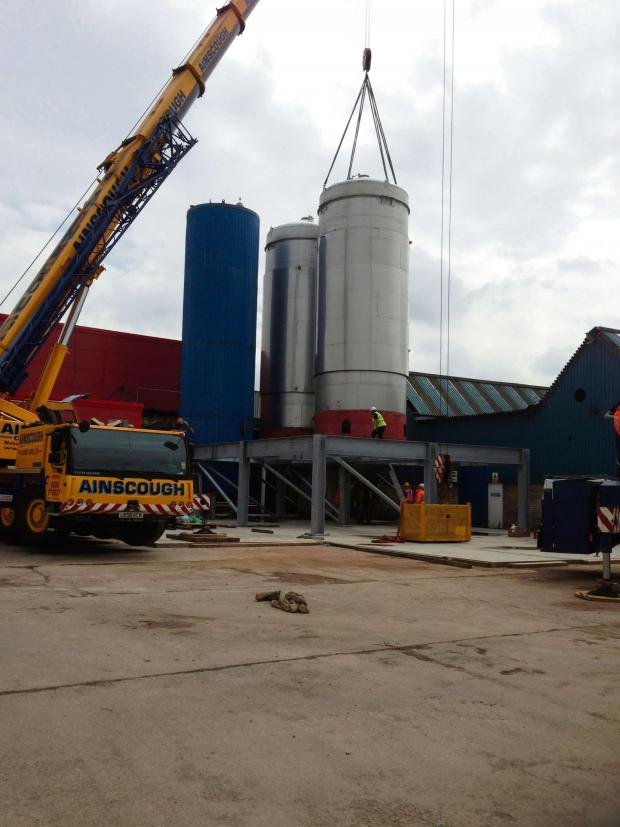 Malvern Gazette: BIG TANKS: The first large fermenting tanks (red base) being installed. Each one holds 165,000 litres.