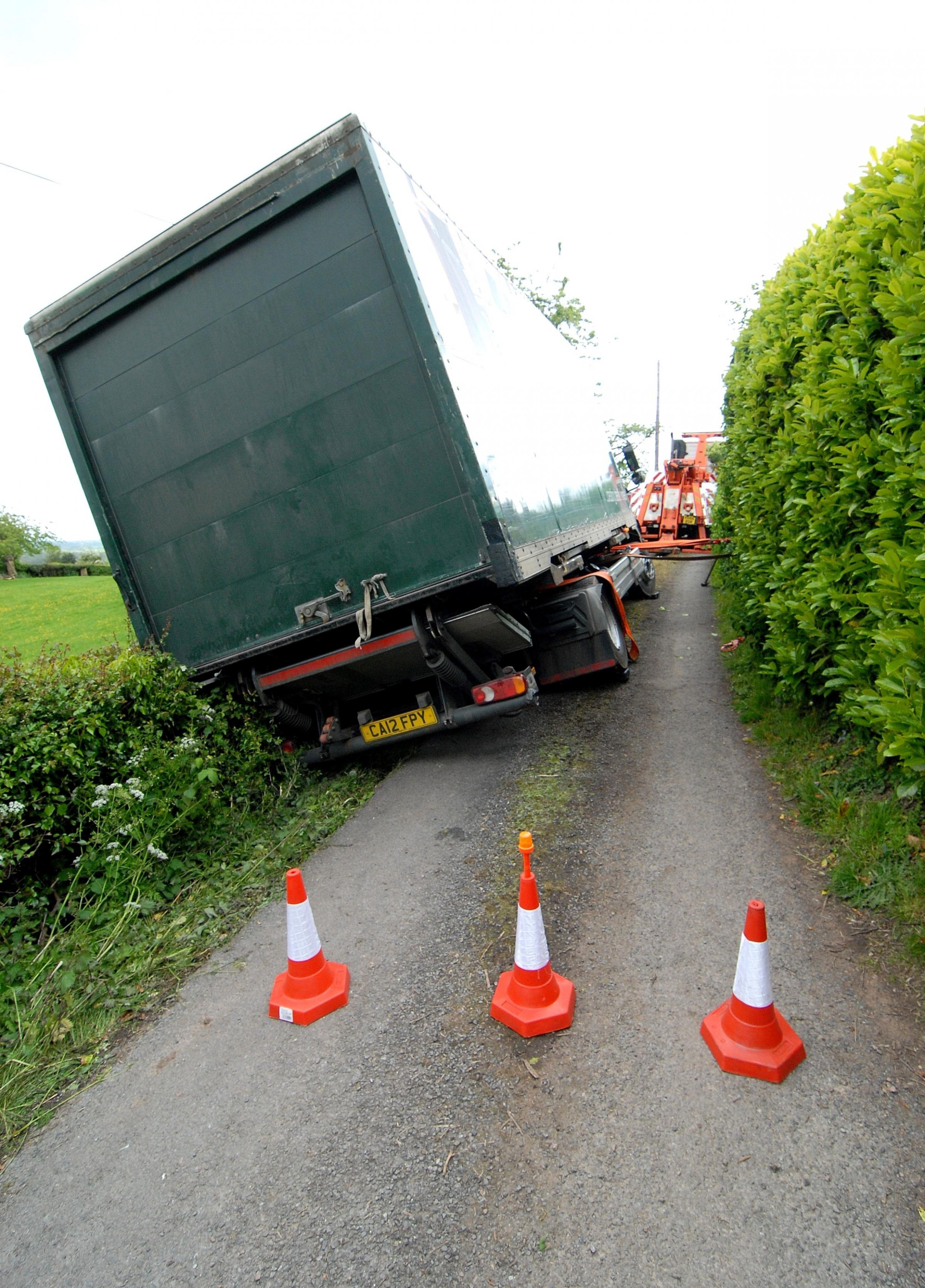 Lorry blocks narrow Worcestershire road after toppling into a hedge