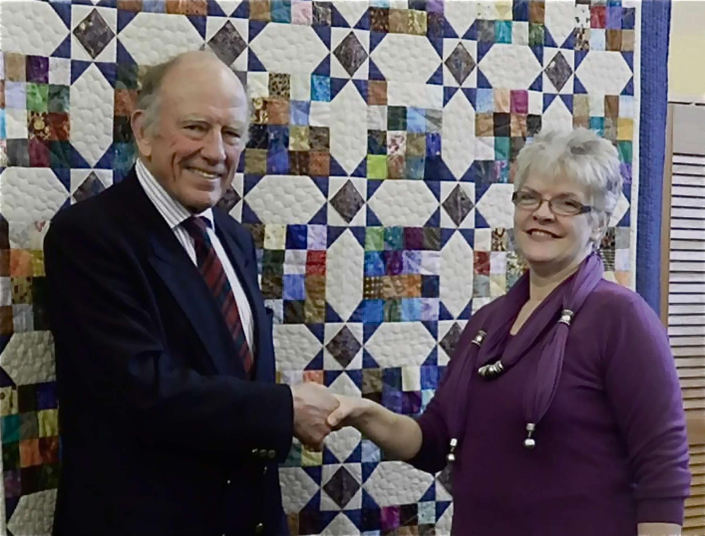 Retired lieutenant colonel Gerry Taggart of Powick, leader of Team Sapper, with Yvonne  Jenkins of Malvern Quilters and the quilt they both hope will help wounded soldiers battle back to better health.