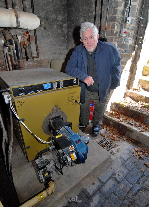 Malvern Gazette: 2414620601. Canon Harold Goddard with the old boiler at Christ Church in Avenue Road, Malvern. Picture by Nick Toogood.