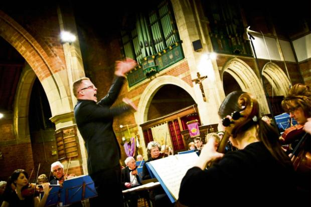 The orchestra's conductor Keith Slade in action