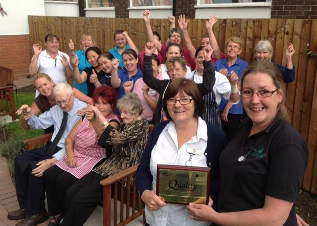 CELEBRATIONS: Liz Baker, care home manager and Claire Brookes, deputy manager, with care home staff, residents and relatives