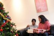 Centrepoint director of policy Balbir Chatrik, right, and resident Comfort Orotayo exchanging gifts after decorating a Christmas tree at the Centrepoint Hostel in Camberwell, London