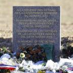 Malvern Gazette: Flowers in front of a monument in the area where a Germanwings aircraft crashed in the French Alps, killing all 150 people aboard (AP)